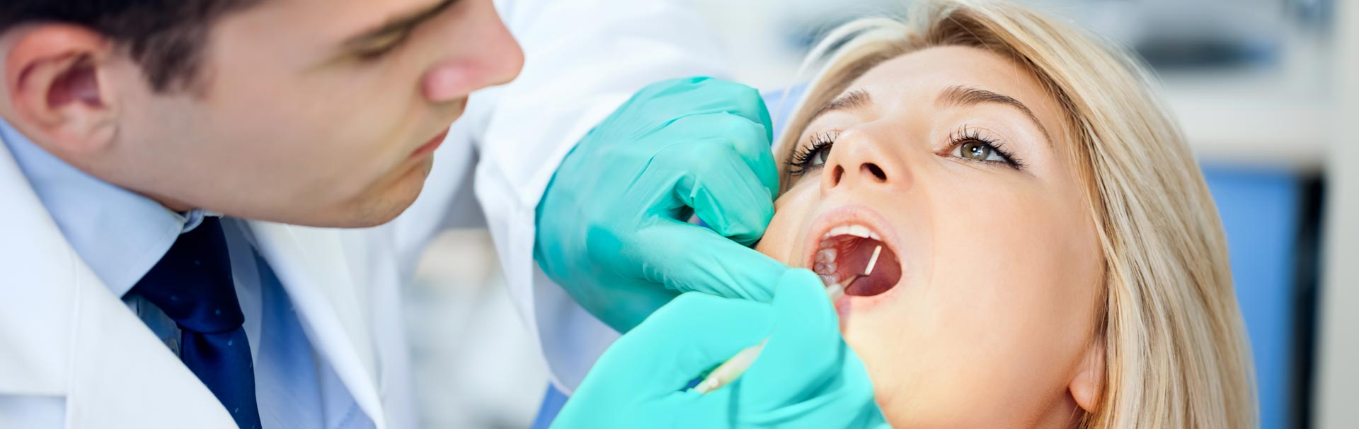 Dentist examining patient mouth for oral cancer
